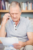 Senior man talking on mobile phone while looking documents Stock Image