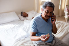 Senior man talking on mobile phone while looking at medicine in bedroom Royalty Free Stock Image