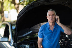 Senior man talking on phone after car breakdown Royalty Free Stock Photography