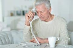 Senior man talking on phone. Sitting near window Stock Images
