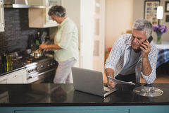 Senior man talking on phone while woman cooking in kitchen Royalty Free Stock Photos