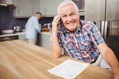 Senior man talking on phone and woman working in kitchen Stock Photos