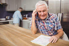 Senior man talking on phone and woman working in kitchen Stock Image