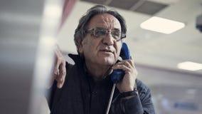 Senior man talking on public payphone Stock Image