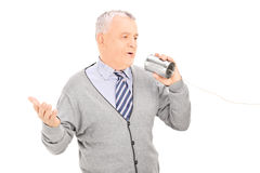 Senior man talking through a tin can phone Royalty Free Stock Image