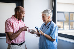 Senior man talking to doctor while pointing at blood pressure. Senior men talking to doctor while pointing at blood pressure gauge at nursing home royalty free stock image