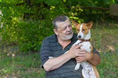 Senior man talking to his cute dog basenji taking it in the hands while resting in summer park Royalty Free Stock Image