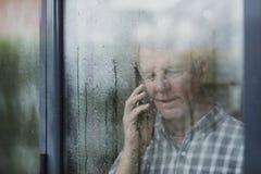 Senior Man Using Phone At Window Stock Photography