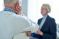 Senior Man Talking to Therapist. Back view  of sad senior men talking to female therapist during consultation, copy space Stock Photos