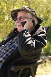 Senior man talks on cell phone. A senior citizen, age 83, uses his cell phone while he sits outside and enjoys the fresh air Royalty Free Stock Photos