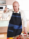 Senior man tasting from spoon Stock Photo