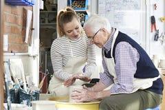 Senior Man With Teacher In Pottery Class. Senior Man And Teacher In Pottery Class stock photos