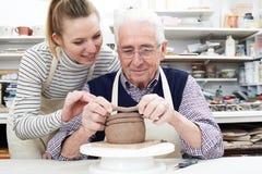 Senior Man With Teacher In Pottery Class. Senior Man With Teacher Working In Pottery Class stock photos