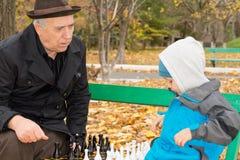 Senior man teaching his grandson chess Royalty Free Stock Images