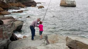 Senior man teaching to child how fishing with rod stock video