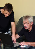 Senior man and teenager on laptop Royalty Free Stock Photos
