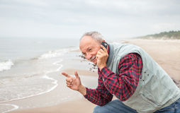 Senior man with a telephone on sea background Royalty Free Stock Image