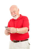 Senior Man Text Messaging. Senior man enjoys text messaging on his cell phone.  Isolated on white Royalty Free Stock Images
