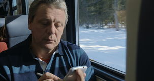 Senior man texting on cell phone in train. Senior man traveling by train and typing text message on smartphone using pen. From time to time he looking at winter stock footage
