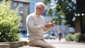 Senior man texting message on smartphone in city stock footage