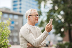 Senior man texting message on smartphone in city. Technology, people, lifestyle and communication concept - senior man texting message on smartphone in city royalty free stock images