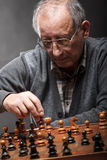 Senior man thinking about his next move in a game of chess Royalty Free Stock Images