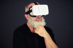 Senior man is thinking about something in virtual reality Stock Images
