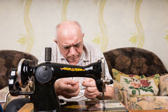Senior Man Threading Needle of Sewing Machine Royalty Free Stock Photography