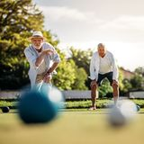 Senior man throwing a boules standing in position. Elderly men playing boules in a playground with his playmate standing in the background. Old men in hat stock photography