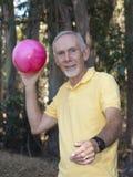 Senior man throwing large ball Stock Photos