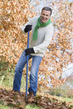 Senior man tidying autumn leaves Royalty Free Stock Photography