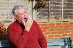 Senior man tired and yawning. Stock Image