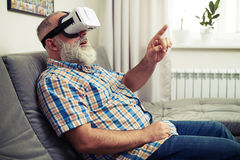 Senior man touch something with his finger using VR glasses. Senior Caucasian man touch something with his finger using VR headset glasses Stock Photos