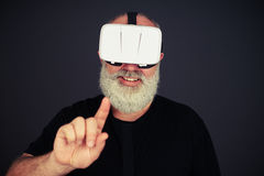 Senior man touch something wearing hi-tech VR headset Stock Images