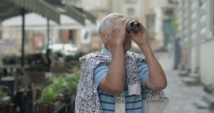 Senior man tourist exploring town. Looking in binoculars. Travel Lviv, Ukraine. Senior male tourist exploring town and looking in binoculars. Traveling in Lviv stock video