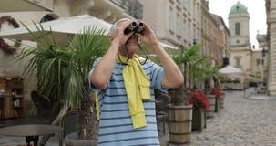 Senior man tourist exploring town. Looking in binoculars. Travel Lviv, Ukraine. Senior male tourist exploring town and looking in binoculars. Traveling in Lviv stock video footage