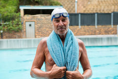 Senior man with towel over his shoulders standing at poolside Royalty Free Stock Photography