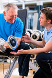 Senior man and trainer at exercise in gym Stock Photography