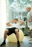 Senior man and trainer in a fitness club Stock Photography