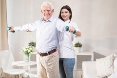 Senior man training with dumbbells. Senior men training with dumbbells during home physiotherapy Royalty Free Stock Images