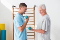 Senior man training with his coach. Senior men training with his coach in fitness studio Stock Images