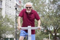 Senior man trains on sporting equipment on open air Stock Photos