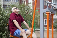 Senior man trains on sporting equipment on open air Royalty Free Stock Image