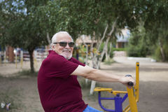 Senior man trains on sporting equipment on open air Royalty Free Stock Photography