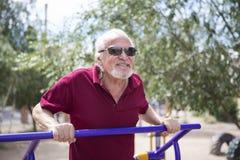 Senior man trains on sporting equipment on open air Stock Photo