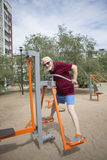 Senior man trains on sporting equipment on open air Royalty Free Stock Images