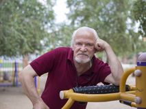 Senior man trains on sporting equipment on open air Stock Photo