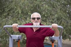Senior man trains on sporting equipment on open air Stock Images