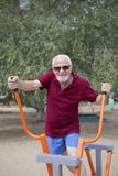 Senior man trains on sporting equipment on open air Royalty Free Stock Photos