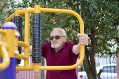 Senior man trains on sporting equipment on open air Stock Image